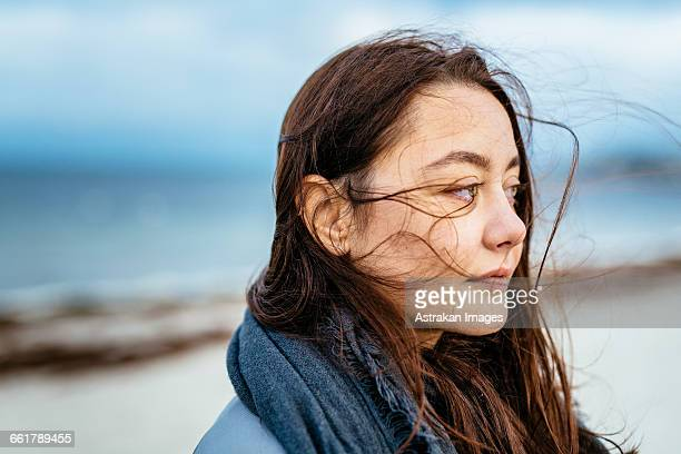 Thoughtful young woman looking away at beach