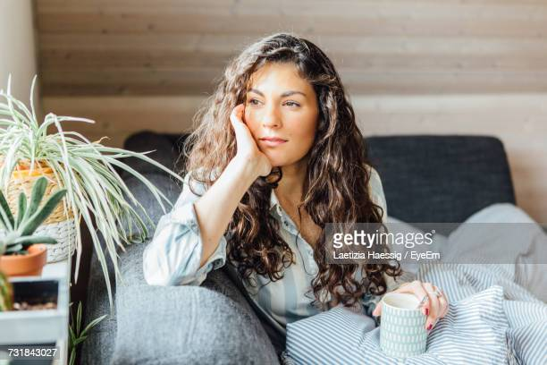 Thoughtful Young Woman Looking Away While Having Coffee On Bed At Home