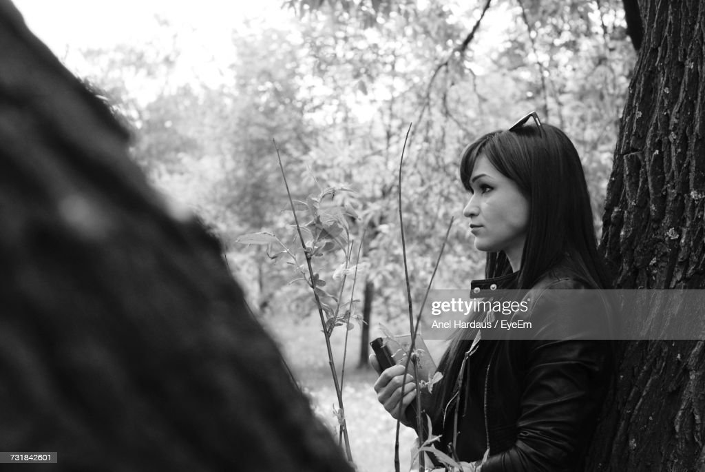 Thoughtful Young Woman Looking Away While Leaning On Tree At Park : Stock Photo