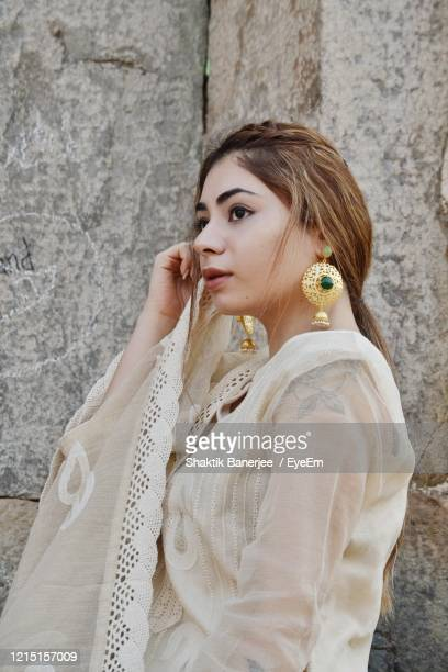 thoughtful young woman looking away while standing by wall - earring stock pictures, royalty-free photos & images