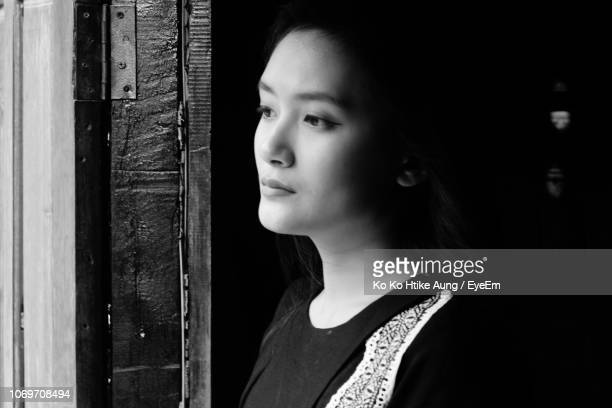 thoughtful young woman looking through window at home - ko ko htike aung stock pictures, royalty-free photos & images