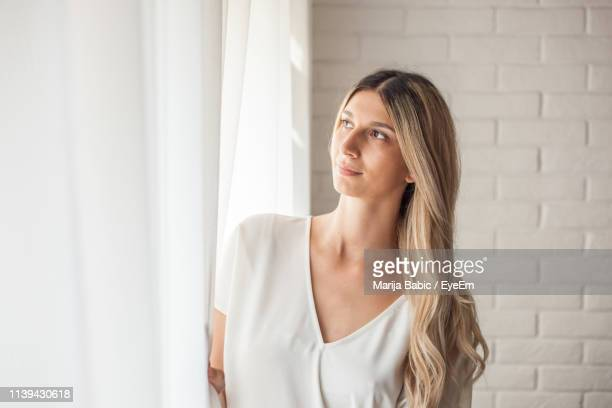 thoughtful young woman looking through window at home - marija mauer stock-fotos und bilder