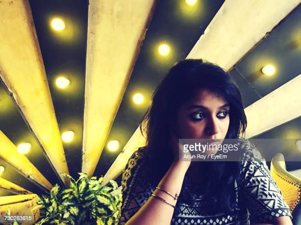 Thoughtful Young Woman Sitting Against Illuminated Wall In Restaurant