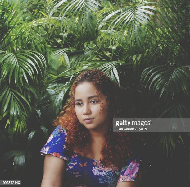 Thoughtful Young Woman Sitting By Plants