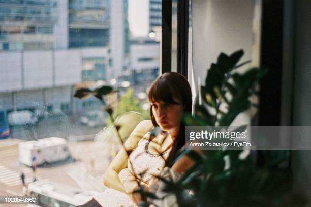 Thoughtful Young Woman Sitting By Window