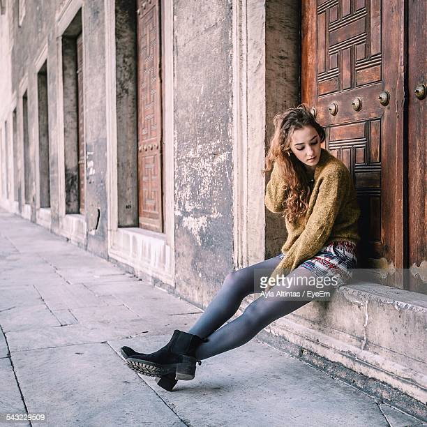 Thoughtful Young Woman Sitting In Front Of Closed Door
