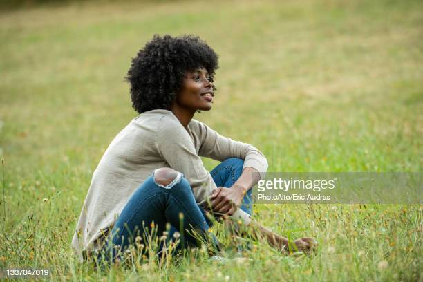 thoughtful young woman sitting in park - one young woman only stock pictures, royalty-free photos & images