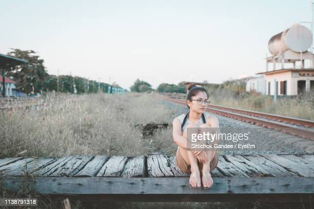 Thoughtful Young Woman Sitting On Boardwalk By Railroad Tracks