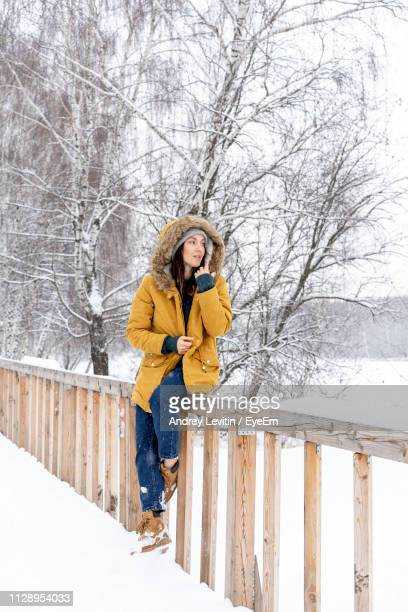 thoughtful young woman sitting on railing in snow covered forest - warme kleding stockfoto's en -beelden