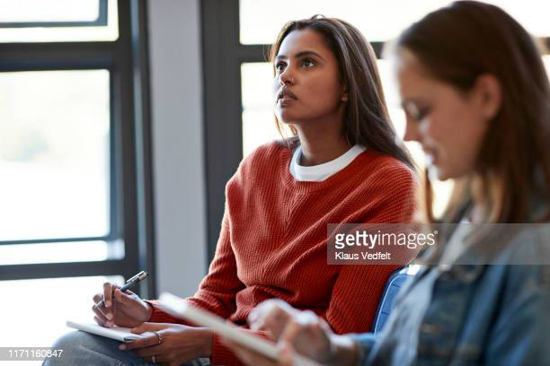 thoughtful young woman sitting with female friend - education stock pictures, royalty-free photos & images