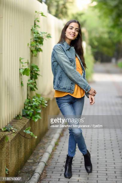 thoughtful young woman smiling while standing on footpath - ダブルデニム ストックフォトと画像