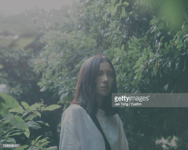 Thoughtful Young Woman Standing By Leaves