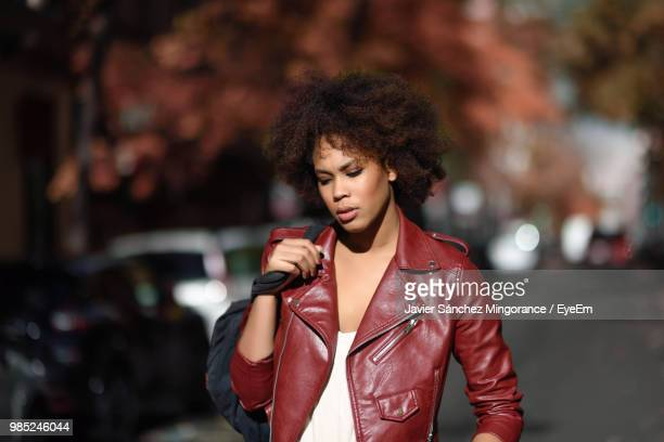 thoughtful young woman standing outdoors - red leather purse stock pictures, royalty-free photos & images