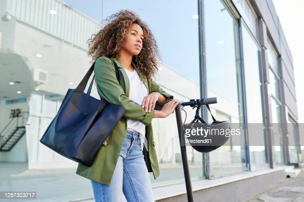 thoughtful young woman standing with electric push scooter on sidewalk - black purse stock pictures, royalty-free photos & images