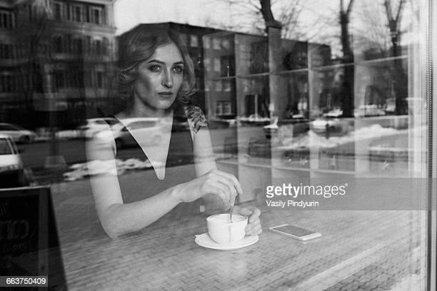 Thoughtful young woman stirring coffee in coffee shop