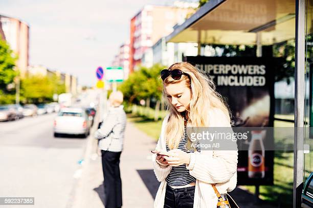 Thoughtful young woman using phone while waiting near bus stop at sidewalk
