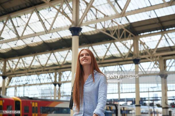 thoughtful young woman walking at railroad station - architecture stock pictures, royalty-free photos & images