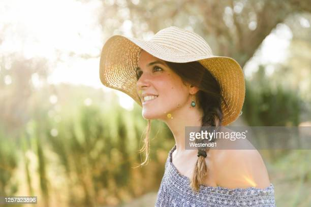 thoughtful young woman wearing sun hat during sunny day - off shoulder stock pictures, royalty-free photos & images