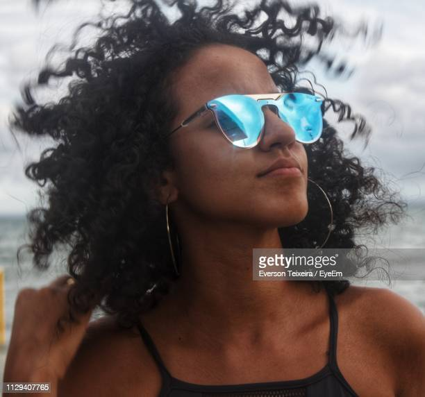 thoughtful young woman wearing sunglasses at beach - コイリーヘア ストックフォトと画像
