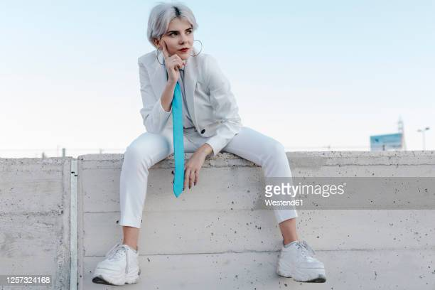 thoughtful young woman wearing white suit sitting on retaining wall against clear sky - capelli grigi foto e immagini stock