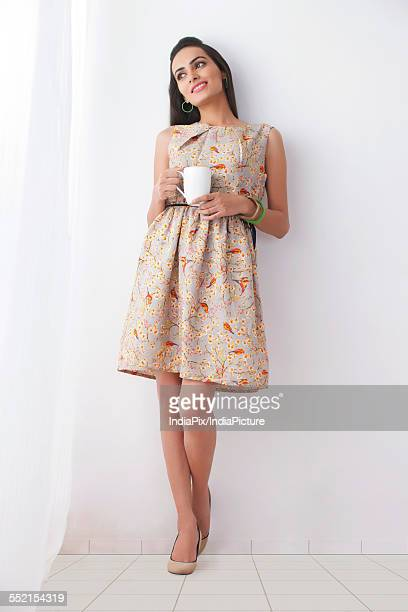 Thoughtful young woman with coffee cup leaning against white wall
