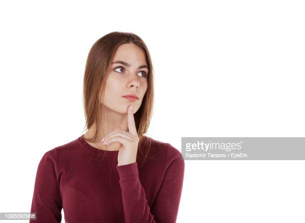 thoughtful young woman with finger on chin looking away against white background - langärmlig stock-fotos und bilder