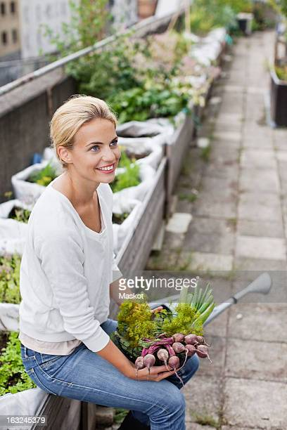 Thoughtful young woman with freshly harvested vegetables at urban garden