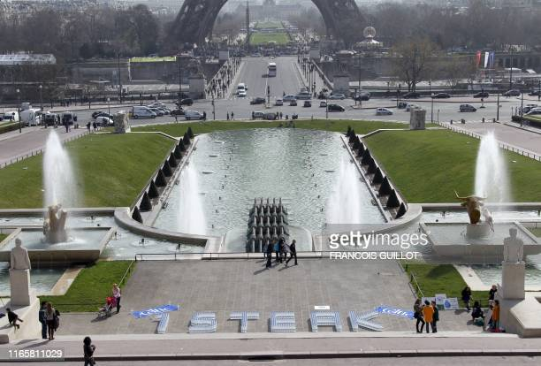 A thousand 15 liter bottles of water with blue caps are displayed by members of the collectif Viandeinfo to form the word one steak near the Eiffel...