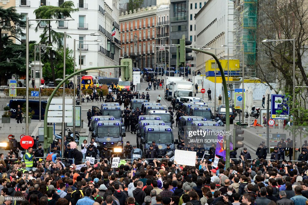 A thousand people gather in front of fences blocking the street leading to the Spain's parliament (Las Cortes) during an anti-government demonstration in Madrid on April 25, 2013. Police in Madrid arrested today four members of anarchist groups suspected of plotting to set fire to a bank and 11 people who blocked access to a university ahead of an anti-government demonstration.