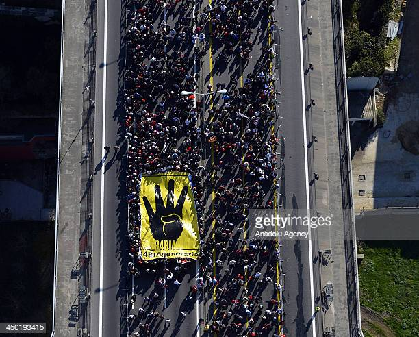 Thousands and also a group carryng a giant Rabaa sign banner attend the public walk through Bosphorus within the The 35th Istanbul Marathon on...