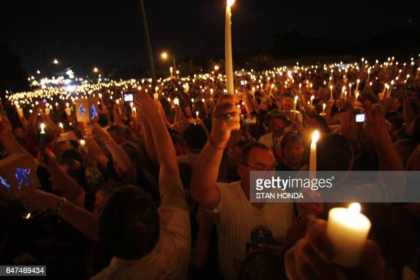 Thousands hold up candles during a candlelight vigil on the eve of the 30th anniversary of Elvis Presley's death 15 August 2007 in front of...