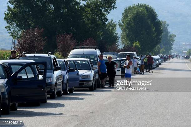 Thousands of Albanians form an enormous queue of cars at the Greek border on August 14 as they rushed to re-enter the Greece for work ahead of new...
