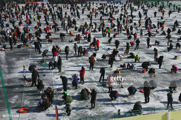 Thousands of anglers fish through holes created in the surface of a frozen river during the annual ice fishing festival in Hwacheon some 120...