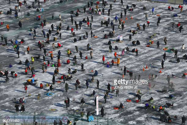TOPSHOT Thousands of anglers fish through holes created in the surface of a frozen river during the annual ice fishing festival in Hwacheon some 120...
