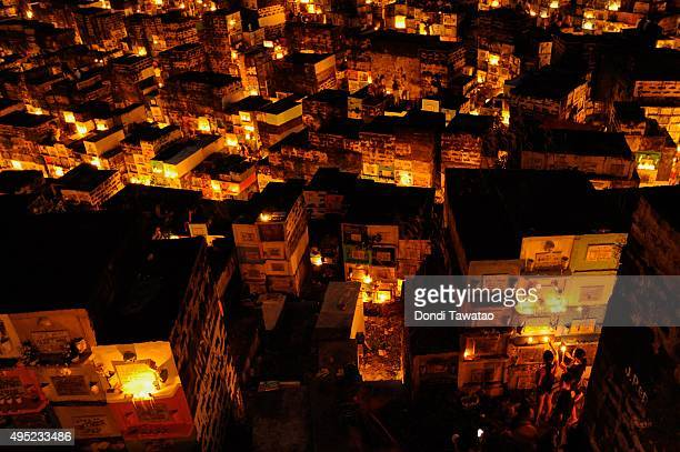 Thousands of apartment style tombstones are illuminated at night with candles at a public cemetery on November 1 2015 in Marikina City Philippines...