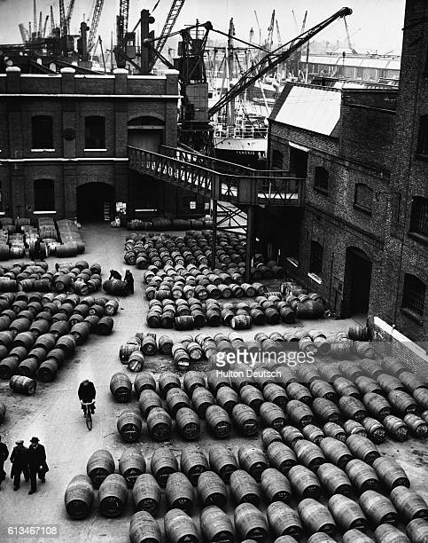 Thousands of barrels of wines and spirits such as Burgundy Sherry and Port from Spain France and Portugal are offloaded and stored at London Docks in...