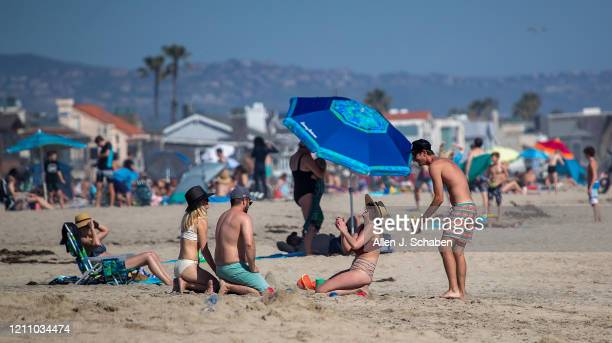 Thousands of beach-goers enjoy a warm, sunny day at the beach amid state-mandated stay-at-home and social distancing mandate to stave off the...