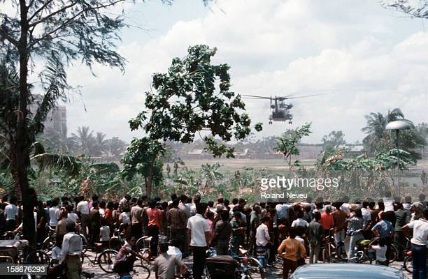 Thousands of Cambodians gather behind a school perimeter fence near the American embassy to witness the final evacuation of US and foreign nationals...