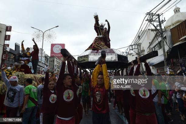 Thousands of Catholic devotees carrying their replicas of the Black Nazarene walk along a street during the blessing of the replicas near Quiapo...