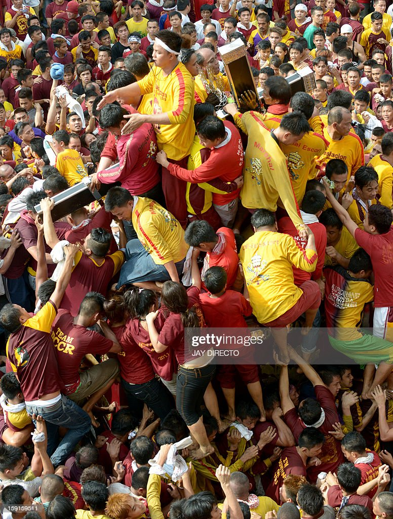 Thousands of Catholic devotees jostle for positions as they climb over one another to try to kiss the cross (C) draped on the statue of Black Nazarene during the annual procession in honor of the c...