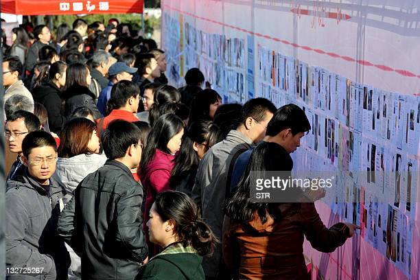 Thousands of Chinese single people check information cards put up on a wall as they take part in a matchmaking fair for employees from China's...