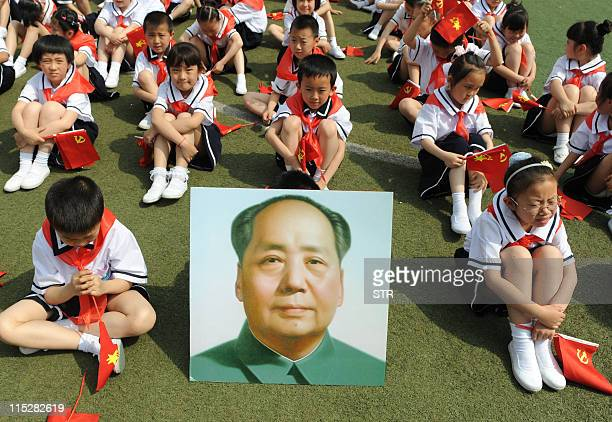 Thousands of Chinese students holding Communist flags sit beside a portrait of China's late leader Mao Zedong as they gather to mark the 90th...