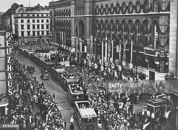 Thousands of citizens throng the streets to greet the arrival of the American delegation to the Olympic Games in Berlin