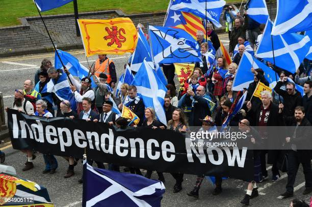 Thousands of demonstrators carry Saltire flags the national flag of Scotland as they march in support of Scottish independence through the streets of...