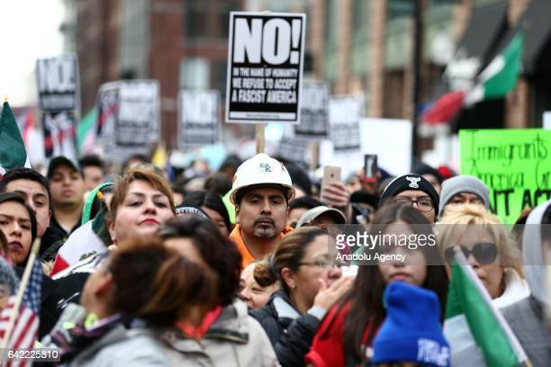 Thousands of demonstrators hold banners during a rally against US President Donald Trump's order and his recent policies regarding cracking down on...