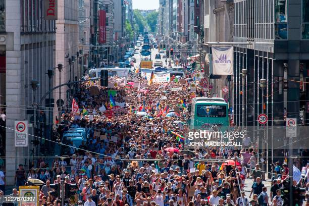 "Thousands of demonstrators march down the Friedrichstrasse street as they take part in a demonstration by the initiative ""Querdenken-711"" with the..."