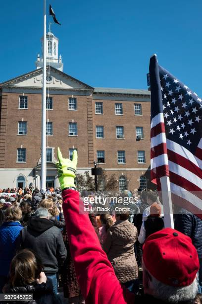 Thousands of demonstrators outside the Morristown Town Hall with protestors holding up an American Flag and holding up two fingers during the March...