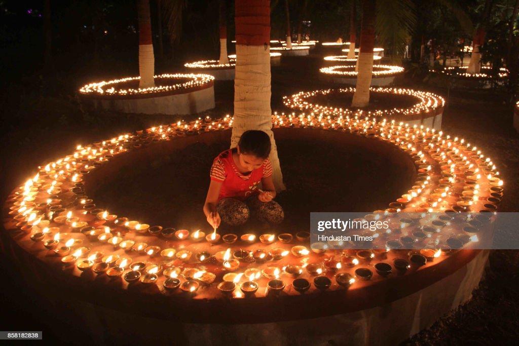 Thousands of Diyas lighten up by devotees during 'Laksha Deepotsav' festival on the occasion of Sharad Purnima at Swami Gagangiri Maharaj Ashram, Manori, Malad, on October 5, 2017 in Mumbai, India. Sharad Purnima is a harvest festival celebrated on the full moon day of the Hindu lunar month of Ashvin, marking the end of the monsoon season. The Kojagari Purnima concerns the observance of the Kojagara Vrata.