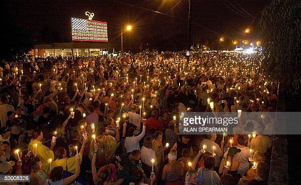 Thousands of Elvis fans brave the rain to give a candlelight tribute to Elvis Presley outside the gates of Graceland 15 August 2002 in Memphis, TN....