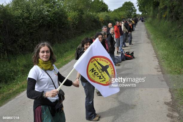 Thousands of farmers environmental activists and opponents hold hands to form a human chain as they take part in a demonstration to protest against a...